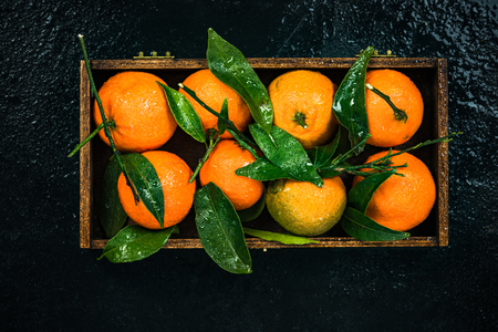 Tangerines or clementines in wooden crate.