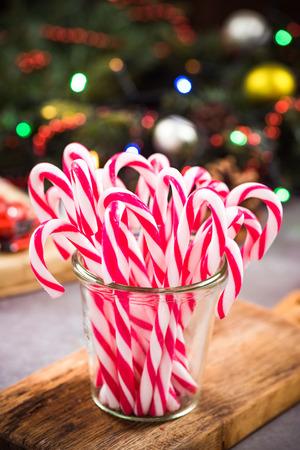 Glas mit festlicher Zuckerstange auf Weihnachtstisch.