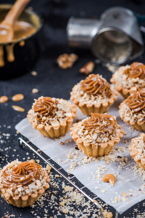 Making omemade caramel cupcakes with walnuts.