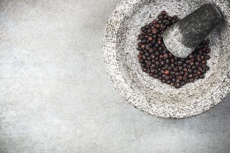 Juniper seeds in granite pestle or mortar.