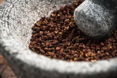 Semi di pepe di timut sihuan in pestello di granito o mortaio.
