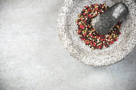 Mixed peppercorn seeds in granite pestle or mortar.