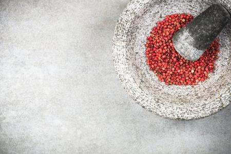 Red peppercorn seed in granite mortar or pestle.