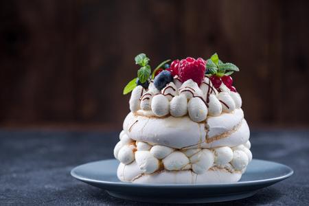 Serving traditional Pavlova dessert with fresh fruits. Stock Photo