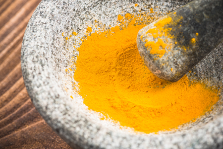 Tumeric powder superfood in granite pestle or mortar. Stock Photo