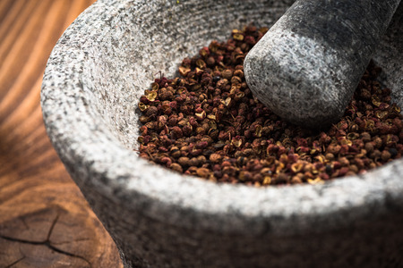 Timut sihuan pepper seeds in granite pestle or mortar. 版權商用圖片 - 112990381
