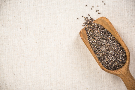Chia seeds on wooden spoon, superfood. Copy space on kitchen cloth with spotlight.
