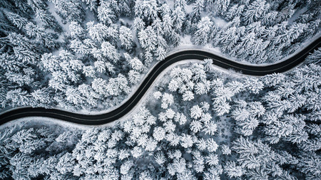 Curvy windy road in snow covered forest, top down aerial view. Stock fotó - 115548072