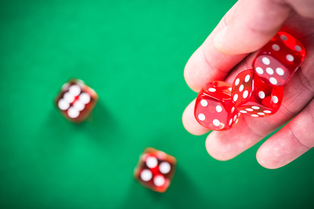 Throwing red poker dices on casino green table.