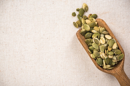 Pumpkin seeds on wooden spoon, superfood. Copy space on kitchen cloth with spotlight. Stock Photo