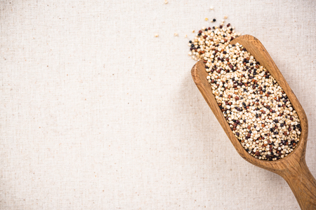 Quinoa seeds on wooden spoon, superfood. Copy space on kitchen cloth with spotlight.