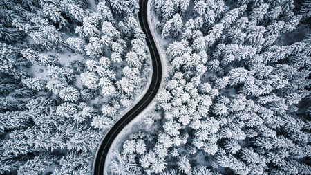 Curvy windy road in snow covered forest, top down aerial view.