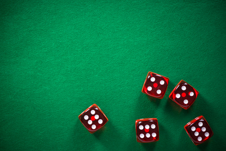 Red poker dices on green casino felt, spotlight background with copy space.