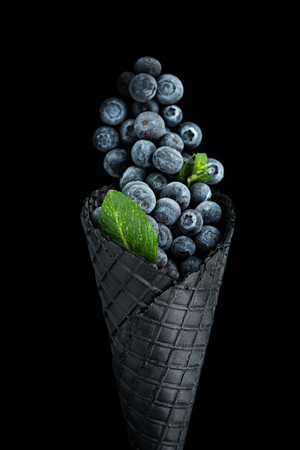 Black wafer cone with frozen blueberry fruits. Healthy ice cream. Stock Photo