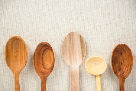 Empty wooden rustic spoons on kitchen cloth. Copy space background.