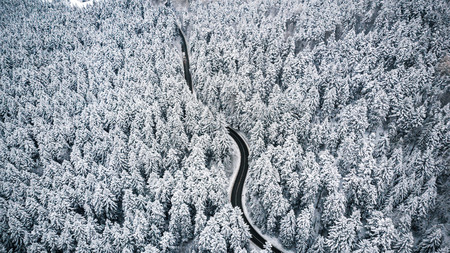 Curvy road line in winter scenery, aerial view.