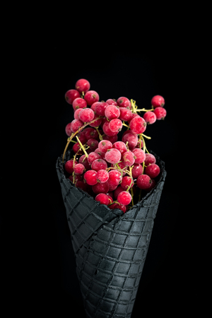 Black wafer cone with frozen redcurrant fruits. Healthy ice cream.