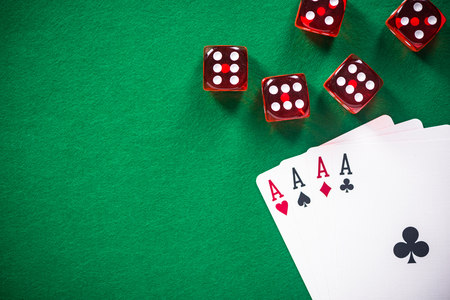 Four aces poker cards and red dices on casino table. Stock Photo