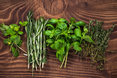 Fresh organic herbs collection on wooden table.