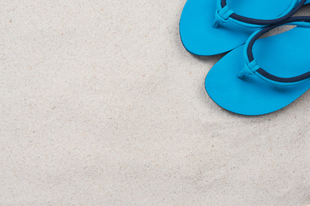 Blue flipflops on sandy beach, overhead view with copy space. 免版税图像