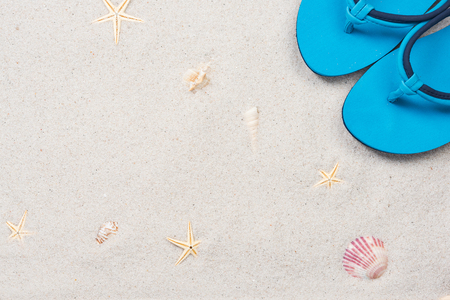 Sunbathing and summer concept, border background. Flipflops on sandy beach. 版權商用圖片