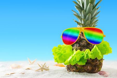 Funny pineapple sunbathing on exotic beach at vacation.