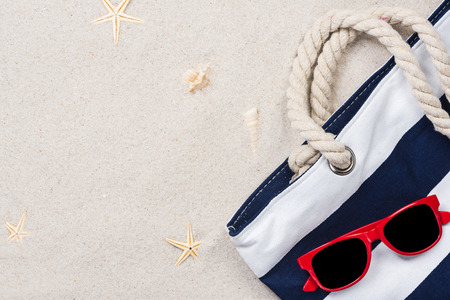 Beach bag on sandy beach, summer vacation background.