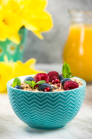 Serving portion of healthy granola with fruits. Фото со стока