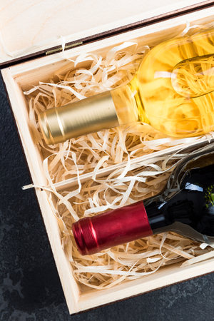 Red and white wine bottles in vintage wooden box. top down view.