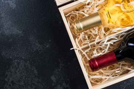 Red and white wine bottles in wooden crate. Boeder dark background with copy space. Imagens