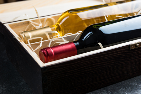 White and red wine bottles in wooden case.