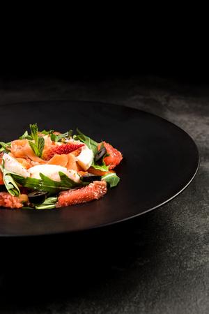 Healthy salad on dark plate.Restaurant dish,healthy eating concept.