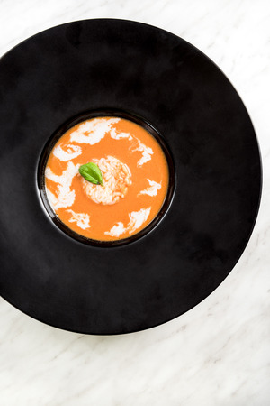 Homemade tomato soup served on dark plate with rice and basil.
