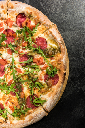 Pepperoni pizza with fresh arugula. Copy space, manu template for restaurant.