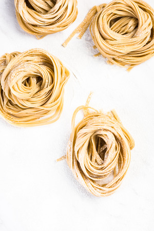 Healthy homemade italian pasta, uncooked on table with flour.