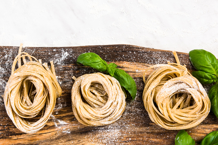 Raw uncooked italian tagliatelle pasta on wooden board.