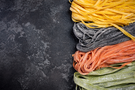 Colorful variety of homemade raw pasta tagliatelle. Dark marble slate background.