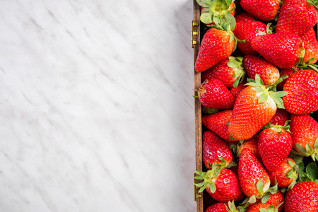 Strawberries in wooden box, border marble background.