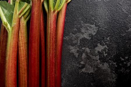 Market fresh rhubarb on dark marble background, copy space.