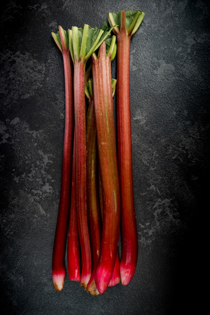 Whole fresh rhubarb steams on dark marble background. Zdjęcie Seryjne