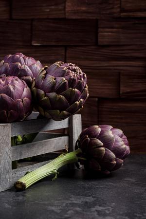 Graden fresh purple artichokes in wooden box.
