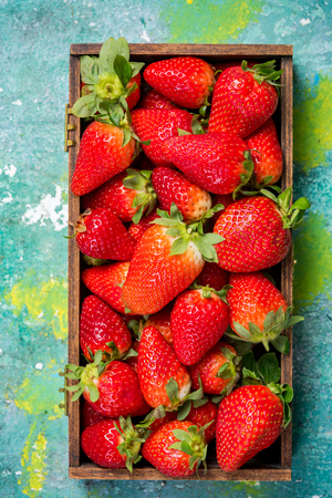 Freshly picked strawberries in wooden box on colorful table.