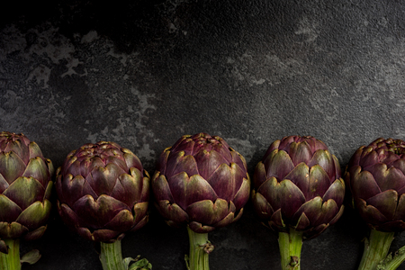 Edible plant, purple artichoke on dark marble background with copy space.