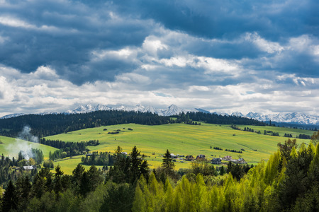 Panoramic view over snowy Tatra mountains peaks and green pasture meadow.