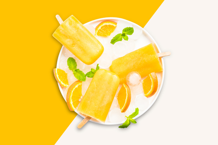 Orange juice popsicles , pastel background.