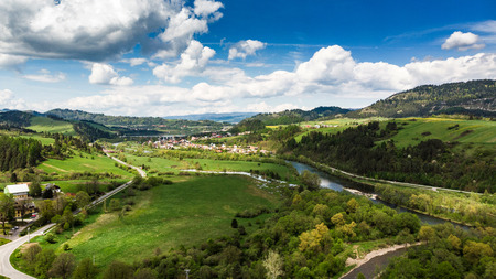 Dunajec river flowing trough valles and countryside in Poland, aerial drone view.