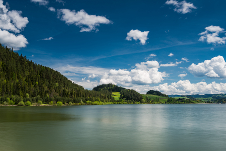 Clear water in Czorsztyn lake and rolling green hills. Clouds over blue sky. Serene and tranquil place. Ecology concept.