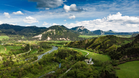 Dunajec river flowing towards Three Crowns mountain peak in Poland. Aerial drone view.