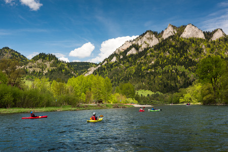 SZCZAWNICA, POLAND  – MAY 2019 : Adventure kayaking and rafting on Dunajec river under Three Crowns mountains peak in Pieniny National Park.