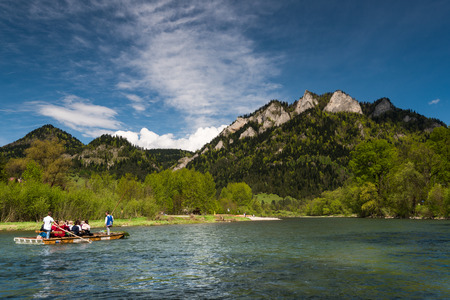 SZCZAWNICA, POLAND  – MAY 2019 : Traditional rafting on Dunajec river under Three Crowns mountains peak in Pieniny National Park.